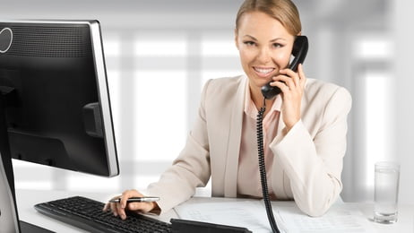 Smiling receptionist answering phone for IT Systems Consultant